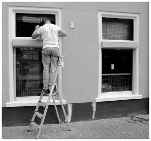 Man on a ladder looking in window